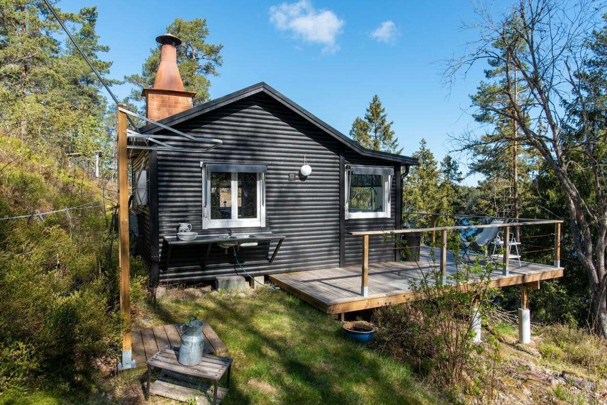 Cabaña de madera negra en el bosque junto al lago